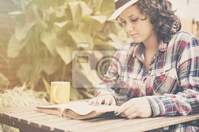 Ein Jugendlicher, der im Garten liest