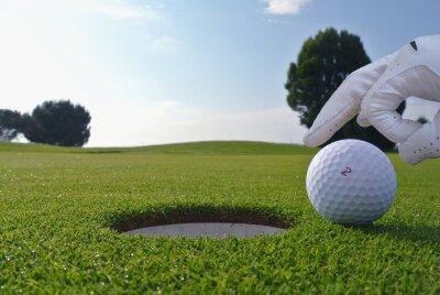 Bild ein Mann, der eine Kugel in einem Golfloch schieben