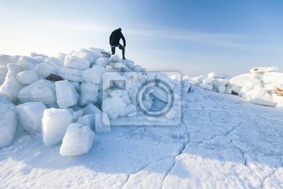 Ein Mann steht auf eisigem Berg.