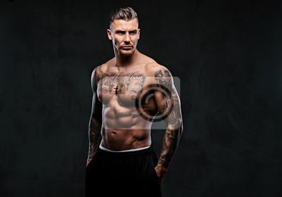 Bild Ein muskulöser tätowierter Mann auf einem dunklen Hintergrund.
