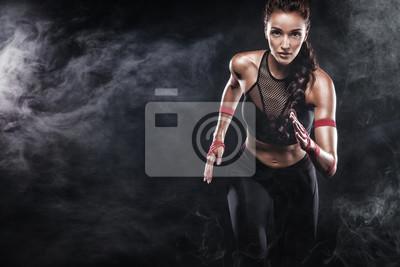 Ein starker Athlet, Frauensprinter, laufend auf dem schwarzen Hintergrund, der in der Sportkleidung, in der Eignung und in der Sportmotivation trägt. Läuferkonzept mit Kopienraum.