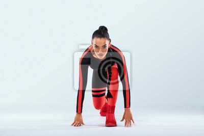 Ein starker athletischer Frauen-Sprinter, der in Sportkleidung, Fitness und Sport motiviert ist. Läuferkonzept mit Kopienraum. Dynamische Bewegung