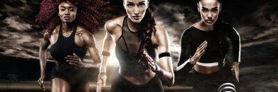 Ein starker athletischer, Frauensprinter, laufend auf den dunklen Hintergrund, der in der Sportkleidung, in der Eignung und in der Sportmotivation trägt. Läufer-Konzept.