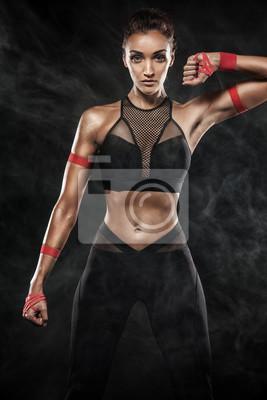 Ein starkes athletisches, Frau auf dem schwarzen Hintergrund, der in der Sportkleidung, in der Eignung und in der Sportmotivation trägt.