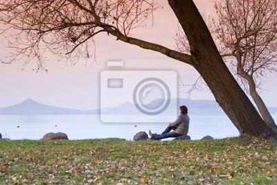 Eine junge Frau / Dame sitzt und eine Entspannung der unter einem Baum