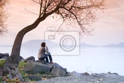 Eine junge Frau / Dame sitzt und eine Entspannung unter einem Baum