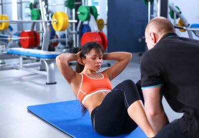 Bild Eine junge Frau mit ihrem Trainer in der Turnhalle