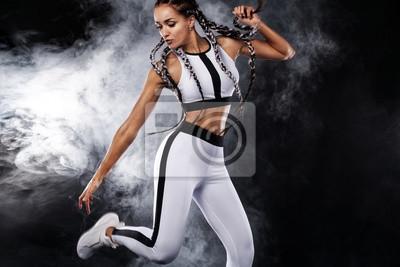 Eine starke athletische Frau auf dem schwarzen Hintergrund, der in der weißen Sportkleidung, in der Eignung und in der Sportmotivation trägt. Sport-Konzept mit Textfreiraum.