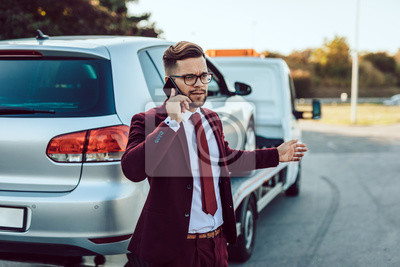 Bild Elegant middle age business man calling towing service for help on the road. Roadside assistance concept.