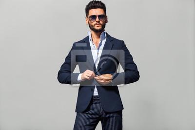 Bild Elegant young handsome man in suite wearing glasses. Studio fashion portrait.