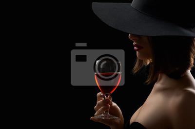 Bild Elegante geheimnisvolle Frau in einem Hut mit einem Glas Rotwein auf