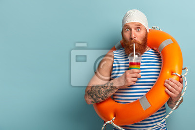 Bild Embarrassed holiday maker drinks cold summer cocktail, spends free time at beach, wears swimcap sailor t shirt, swims with lifebuoy, has surprised expression, models over blue wall with free space