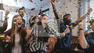 Bild Emotion. Multi-ethnische Fans feiern das Gewinnen. Konfetti 4K Zeitlupe. Leidenschaftliche Unterstützer schreien das Spiel im Fernsehen.