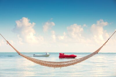 Empty hammock under tall palm trees on tropical beach