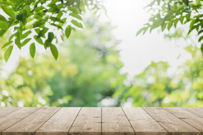 Bild Empty wood table top and blurred green tree in the park garden background - can used for display or montage your products.
