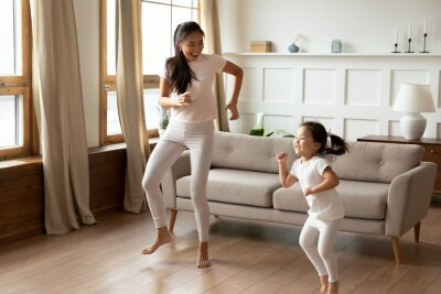 Bild Energetic young vietnamese ethnic mother enjoying playtime with funny crazy asian child daughter, dancing to favorite disco music barefoot in modern living room, hobby weekend pastime indoors.
