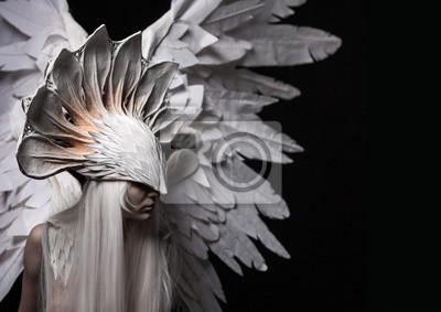 Engel, Kostüm, Konzept, Kino, ein Porträt eines jungen Mädchens und eine weiße Perücke, die eine große weiße Maske und eine große weiße Flügel trägt. Dramatisch