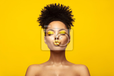 Bild Enjoyed African American Fashion Model portrait . Satisfied Brunette young woman with afro hair style and closed eyes show kiss,creative yellow make up, lips and eyeshadows on colorful background.