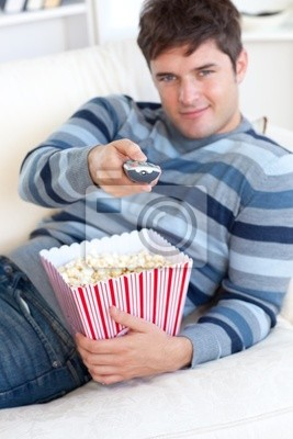 Entspannter junger Mann, Popcorn essen und mit einer Fernbedienung liegend auf t