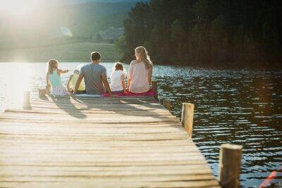 Bild Family sitting at the edge of dock over lake