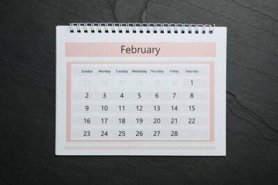 Bild February calendar on black stone background, top view