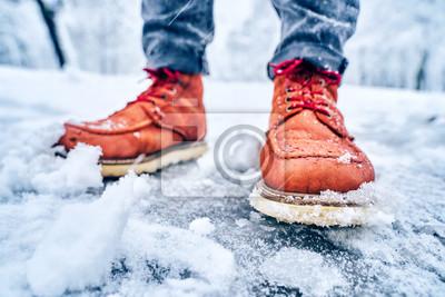 Bild Feet of a man on a snowy sidewalk in brown boots. Winter slippery pawement. Seasonal weather concept