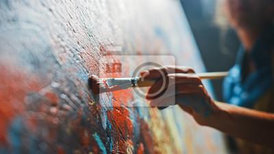 Bild Female Artist Works on Abstract Oil Painting, Moving Paint Brush Energetically She Creates Modern Masterpiece. Dark Creative Studio where Large Canvas Stands on Easel Illuminated. Low Angle Close-up