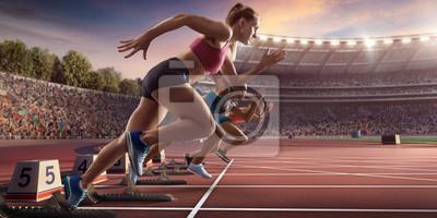 Bild Female athletes sprinting. Three women in sport clothes run at the running track in professional stadium