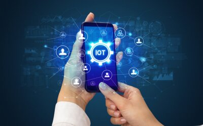 Female hand holding smartphone with IOT abbreviation, modern technology concept