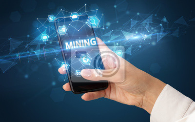 Female hand holding smartphone with MINING inscription, modern technology concept