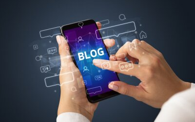 Female hand typing on smartphone with BLOG inscription, social media concept