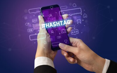 Female hand typing on smartphone with #HASHTAG inscription, social media concept