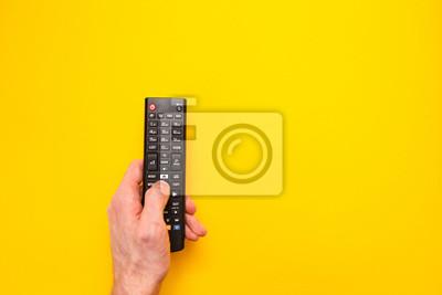 Bild Fernsehfernbedienung in der Hand lokalisiert auf gelbem Hintergrund