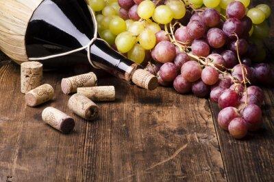 Bild fiasco di vino con uva e turaccioli su tavola di legno