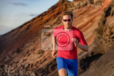 Bild Fit runner man sport athlete trail, running outside on volcano mountain in desert. Motivation and focus during exercise. Fitness and health.