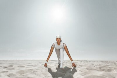 Fit woman sprinter, start running at the desert wearing in white sportswear. Fitness and sport motivation. Runner concept with copy space.