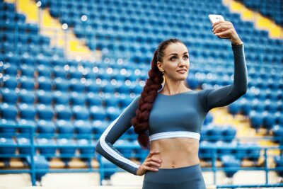 Fitness woman on stadium. Healthy sports lifestyle. Athletic young female in sports wear doing fitness exercise