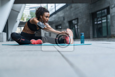 Bild Fitness woman with earphones exercising and stretching outdoors on fitness mat