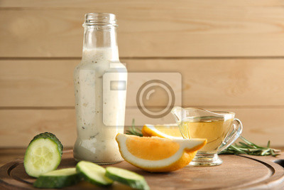 Bild Flasche mit geschmackvollen weißen Soße-, Gurken- und Zitronenscheiben auf hölzernem Brett
