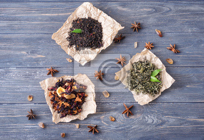 Bild Flat lay composition with different types of dry tea leaves on wooden background