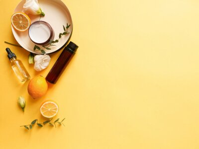 Bild flatlay composition with cream, lotion, oil, flower, citrus and eucalyptus on yellow background. Concept beauty natural vitamin cosmetic product, skin care, copyspace, top view