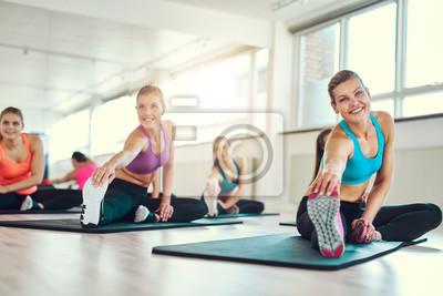 Flexible junge Frauen, die zusammen strecken