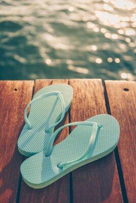 Bild Flip flops at the wooden pier during sunset. Luxury vacation resort. Holiday getaway concept. Vertical, warm toning