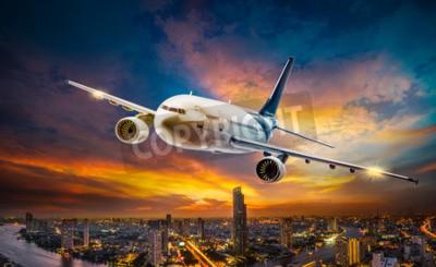Bild Flugzeug für den Transport, der über die Nachtszenenstadt auf schönem Sonnenunterganghintergrund fliegt
