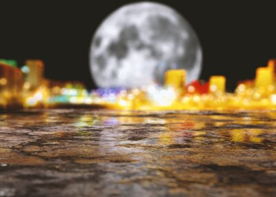 Fondo de asfalto y carretera en la ciudad de noche con luna llena.Luces de farolas y edificios y charcos en el suelo húmedo después de la lluvia
