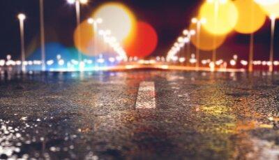 Fondo de asfalto y carretera en la ciudad de noche.Luces de farolas y edificios y charcos en el suelo húmedo después de la lluvia