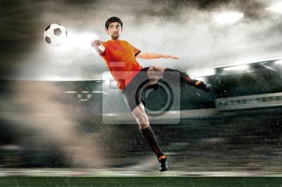 Football-Spieler schlagen den Ball im Stadion
