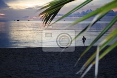 Frau auf einem tropischen Strand bei Sonnenuntergang.