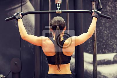 Frau beugt Muskeln auf Kabel-Maschine im Fitnessstudio
