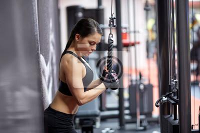 Frau Biegen Arm Muskeln auf Kabel-Maschine in der Turnhalle